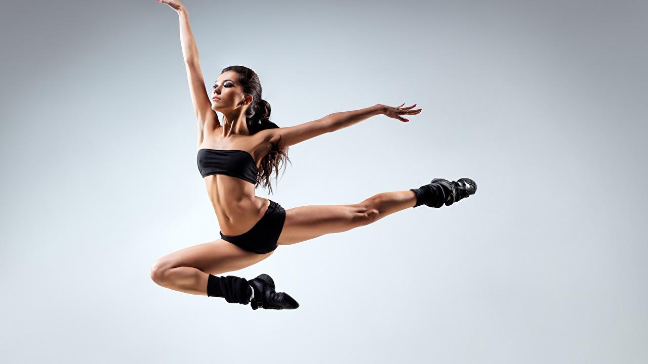Фото брюнетки Танцы Девушки Ноги в прыжке рука сером фоне брюнеток Брюнетка танцуют танцует девушка молодые женщины молодая женщина ног Прыжок прыгать прыгает Руки Серый фон