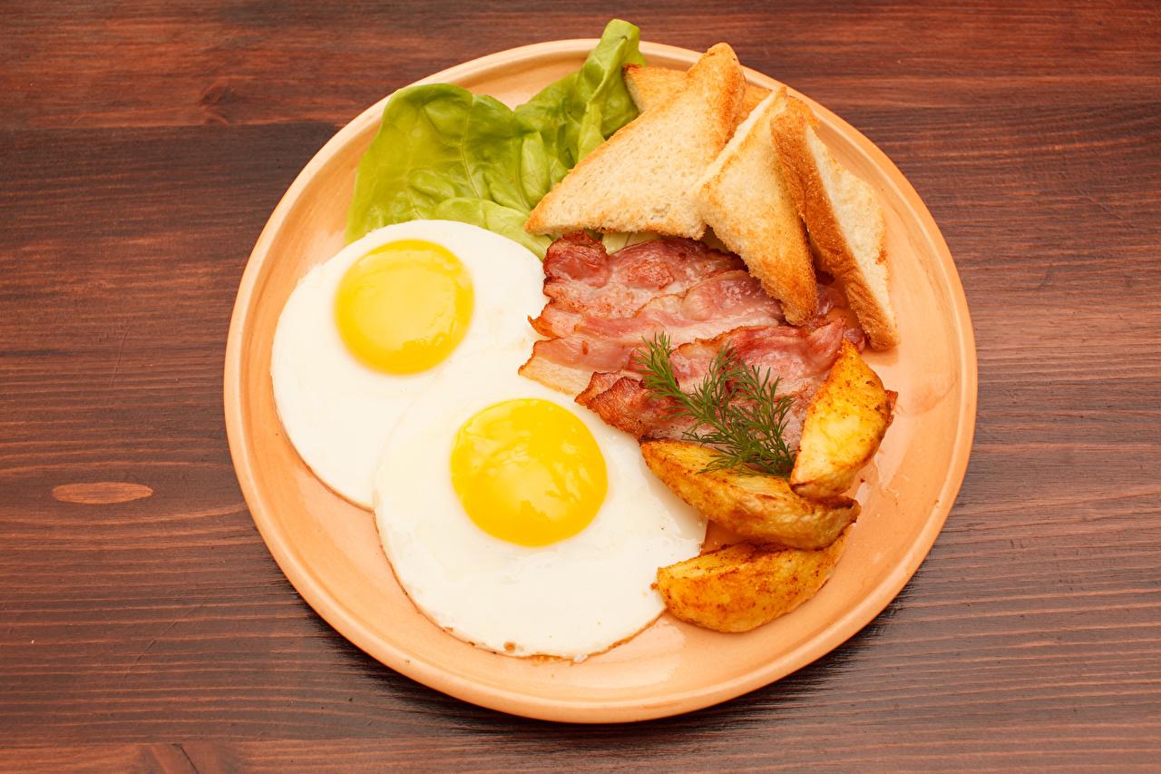Фотографии Продукты питания Тарелка Картофель Хлеб Бекон яичницы Мясные продукты Еда Пища тарелке картошка Яичница глазунья