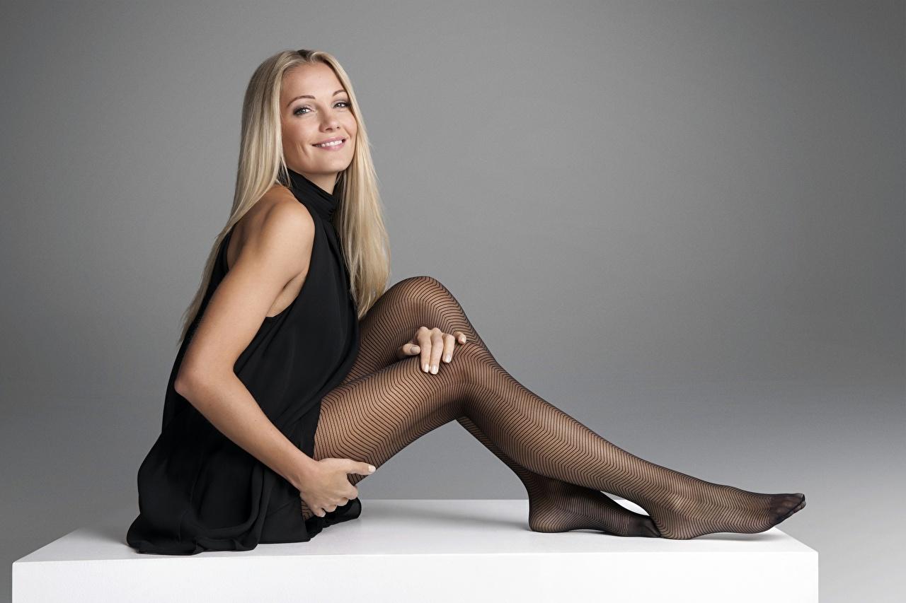 Картинки колготок Блондинка фотомодель улыбается Caroline Fleming Девушки Ноги рука Сидит Серый фон Платье Колготки блондинки блондинок колготках Модель Улыбка девушка молодая женщина молодые женщины ног Руки сидя сидящие сером фоне платья