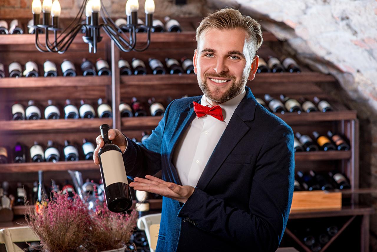 Картинка Мужчины улыбается Вино бутылки классический костюм смотрят Улыбка Костюм костюма костюме Бутылка Взгляд смотрит