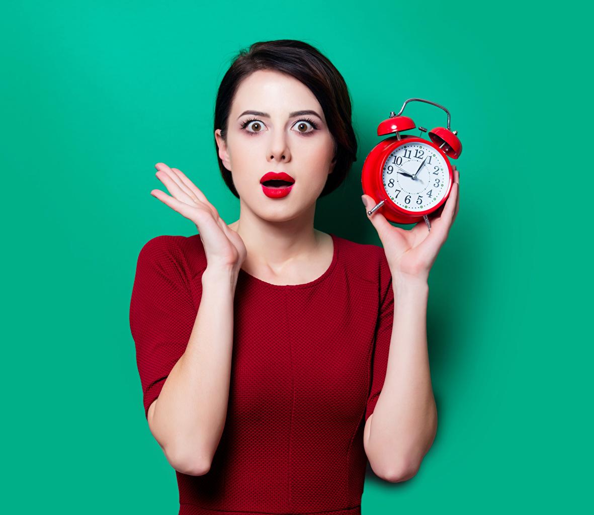 Фотография Брюнетка Удивление Часы Девушки Будильник Руки Цветной фон эмоции изумление