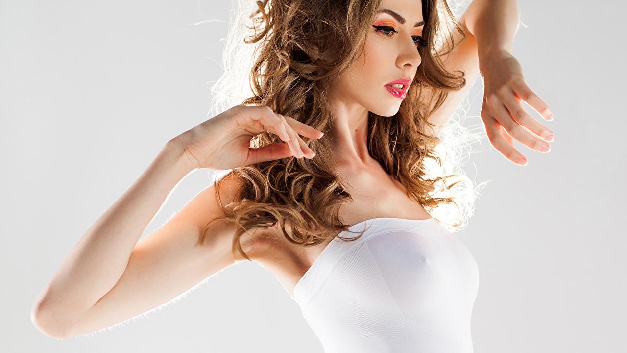 Картинка Шатенка кудри прически Волосы молодая женщина Руки Серый фон шатенки Кудрявые Причёска волос девушка Девушки молодые женщины рука сером фоне