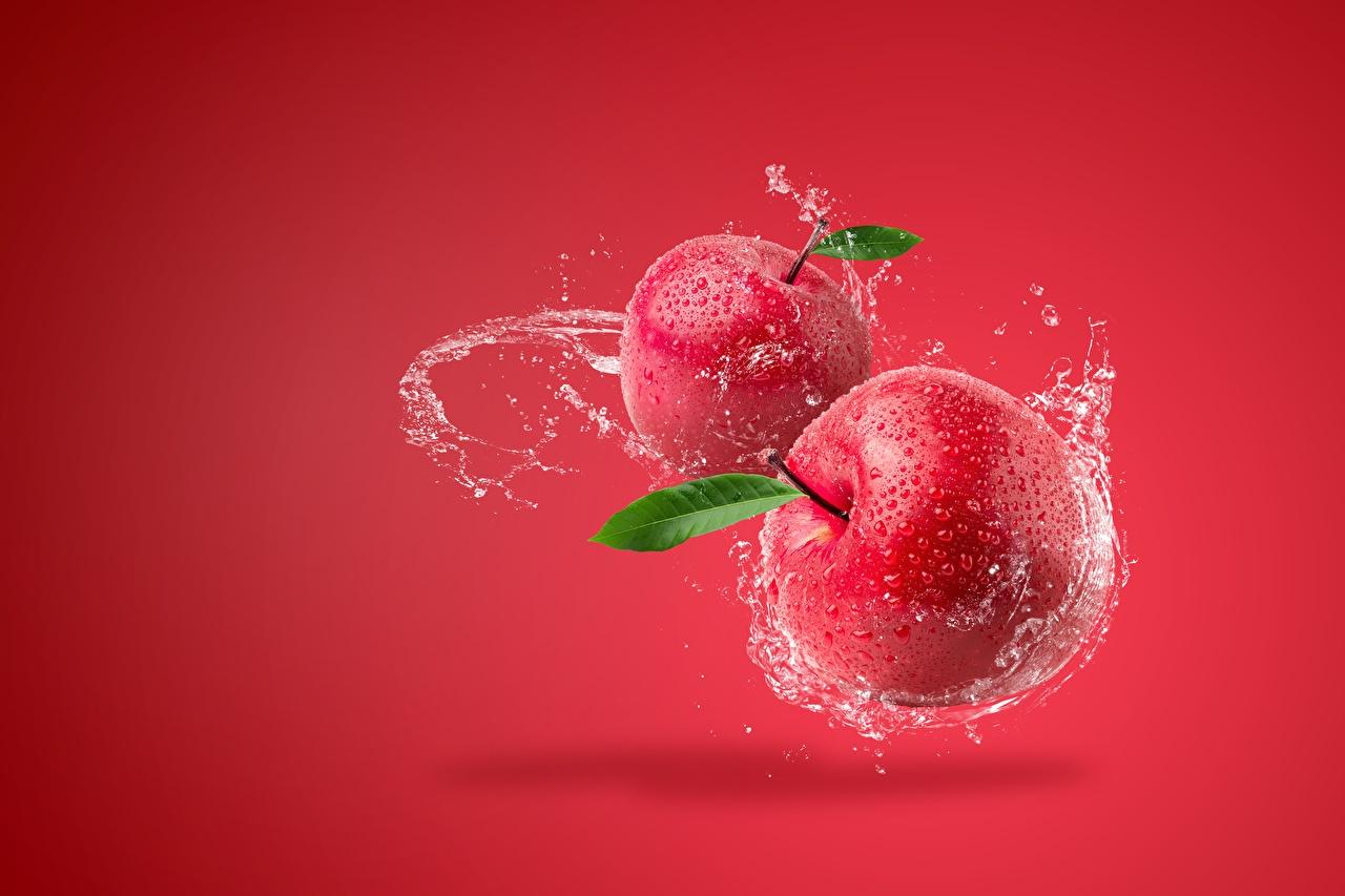 Фотографии Красный Яблоки Брызги Пища Красный фон красная красные красных с брызгами Еда Продукты питания красном фоне