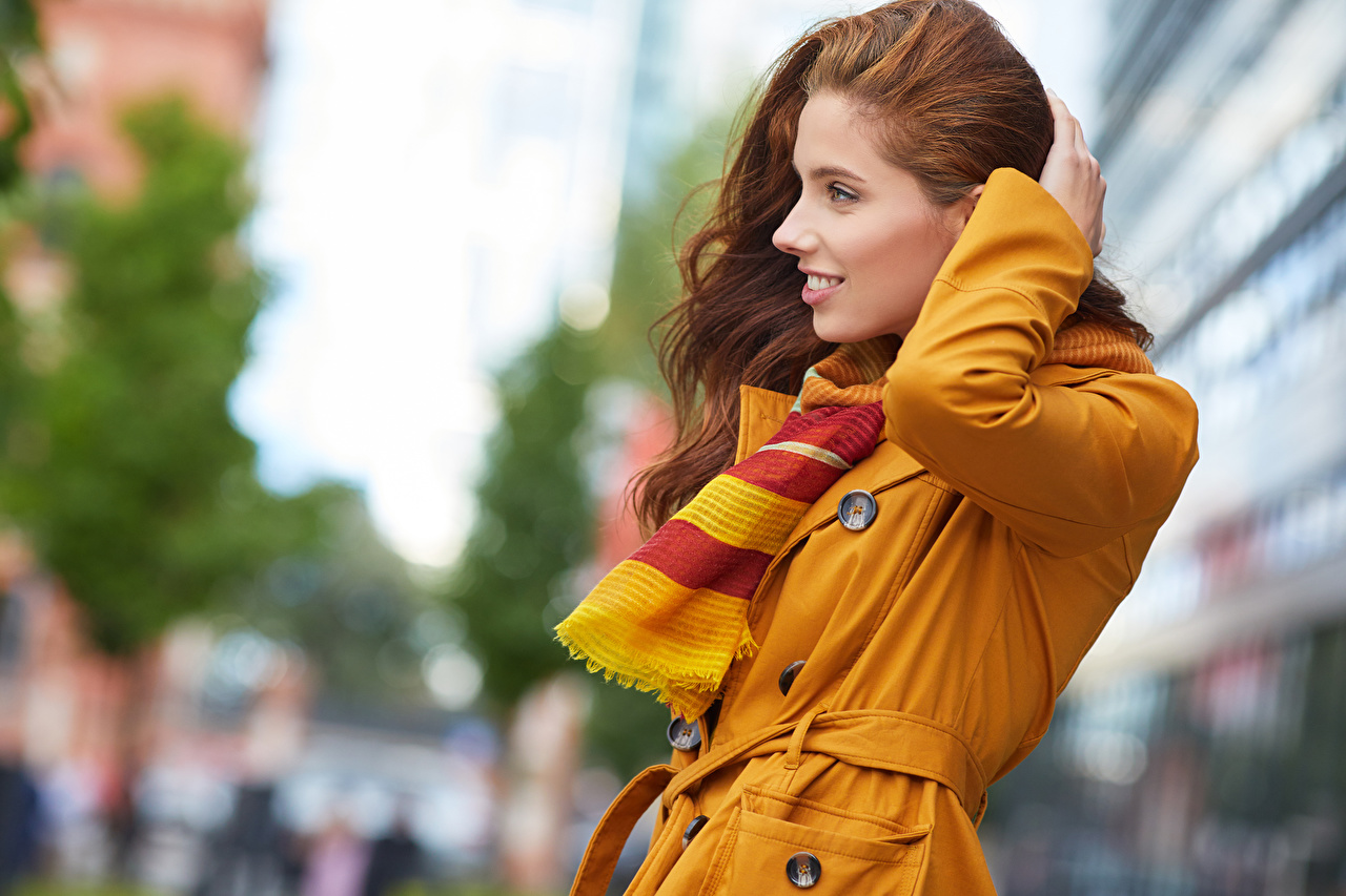 Картинки Рыжая шарфе Улыбка боке Поза молодая женщина смотрят рыжих рыжие Шарф шарфом улыбается Размытый фон позирует девушка Девушки молодые женщины Взгляд смотрит