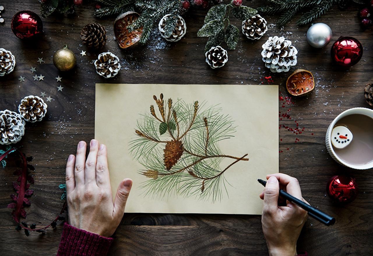 Картинка Новый год Лист бумаги Шар Руки шишка ветка Пальцы Рождество рука Шишки Ветки ветвь Шарики на ветке
