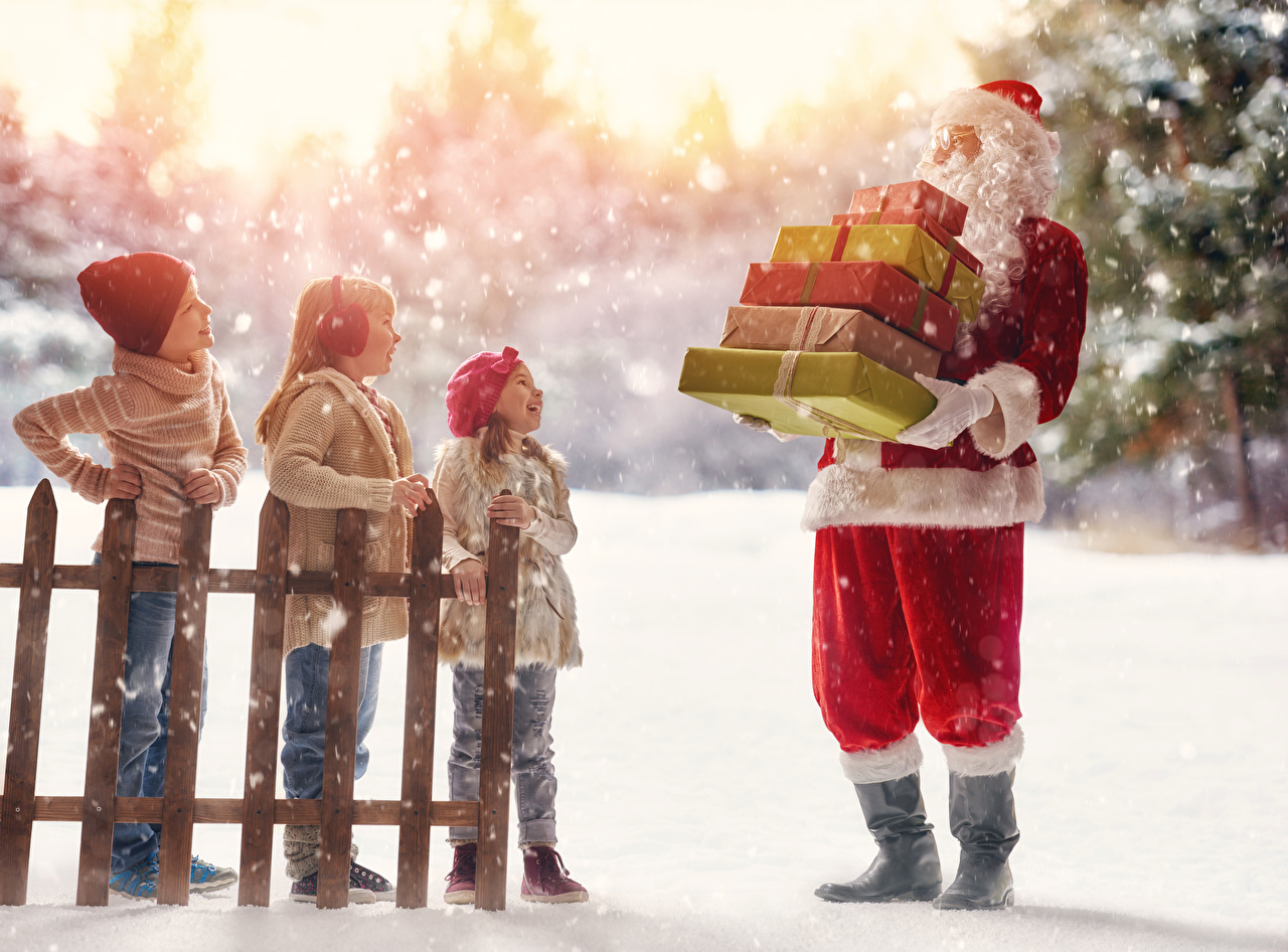 Фото Девочки Мальчики Рождество ребёнок Шапки Санта-Клаус Снег Забор подарок Униформа девочка мальчик мальчишки мальчишка Новый год Дети шапка в шапке Дед Мороз снега снеге снегу забора ограда Подарки забором подарков униформе
