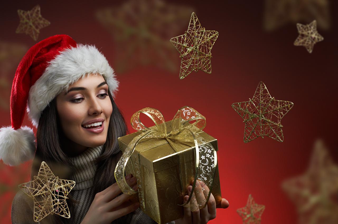 Картинка Новый год Звездочки Улыбка в шапке девушка Подарки коробки Бантик Рождество улыбается шапка Шапки Девушки молодая женщина молодые женщины подарок Коробка коробке подарков бант бантики