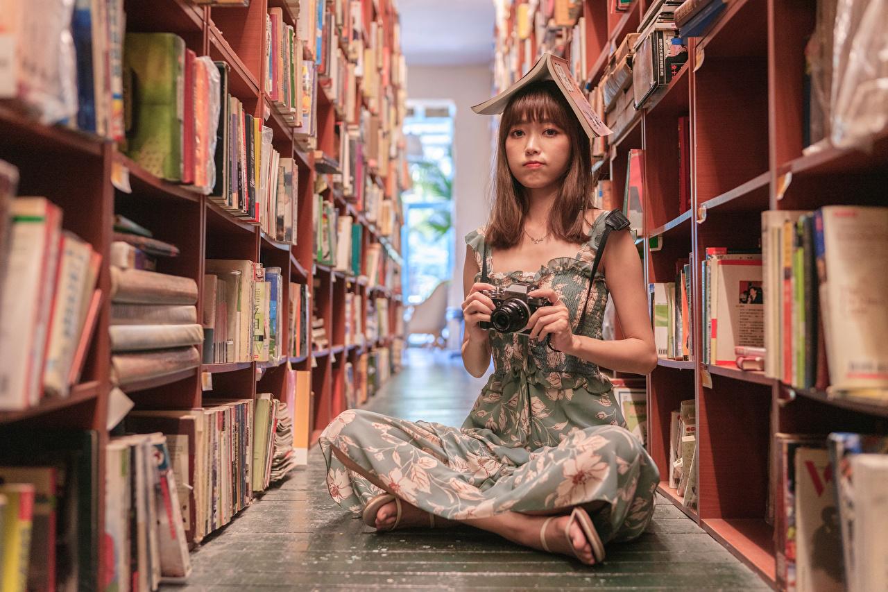 Фотографии Фотоаппарат Библиотека молодая женщина азиатка Сидит книги смотрят платья фотокамера библиотеке девушка Девушки молодые женщины Азиаты азиатки сидя Книга сидящие Взгляд смотрит Платье