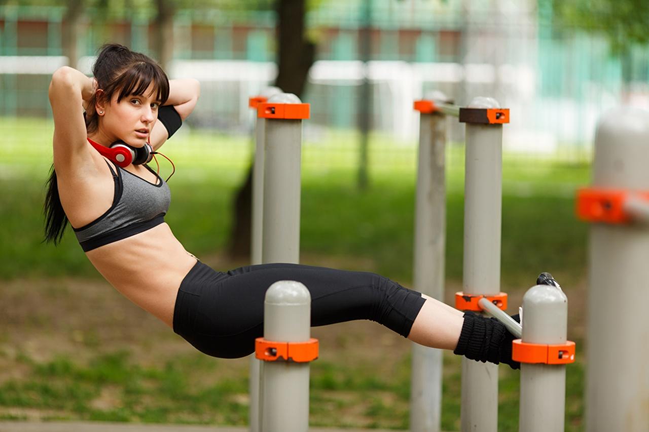 Фотография в наушниках тренируется боке Фитнес девушка ног рука Униформа Наушники Тренировка физическое упражнение Размытый фон Девушки молодая женщина молодые женщины Ноги Руки униформе