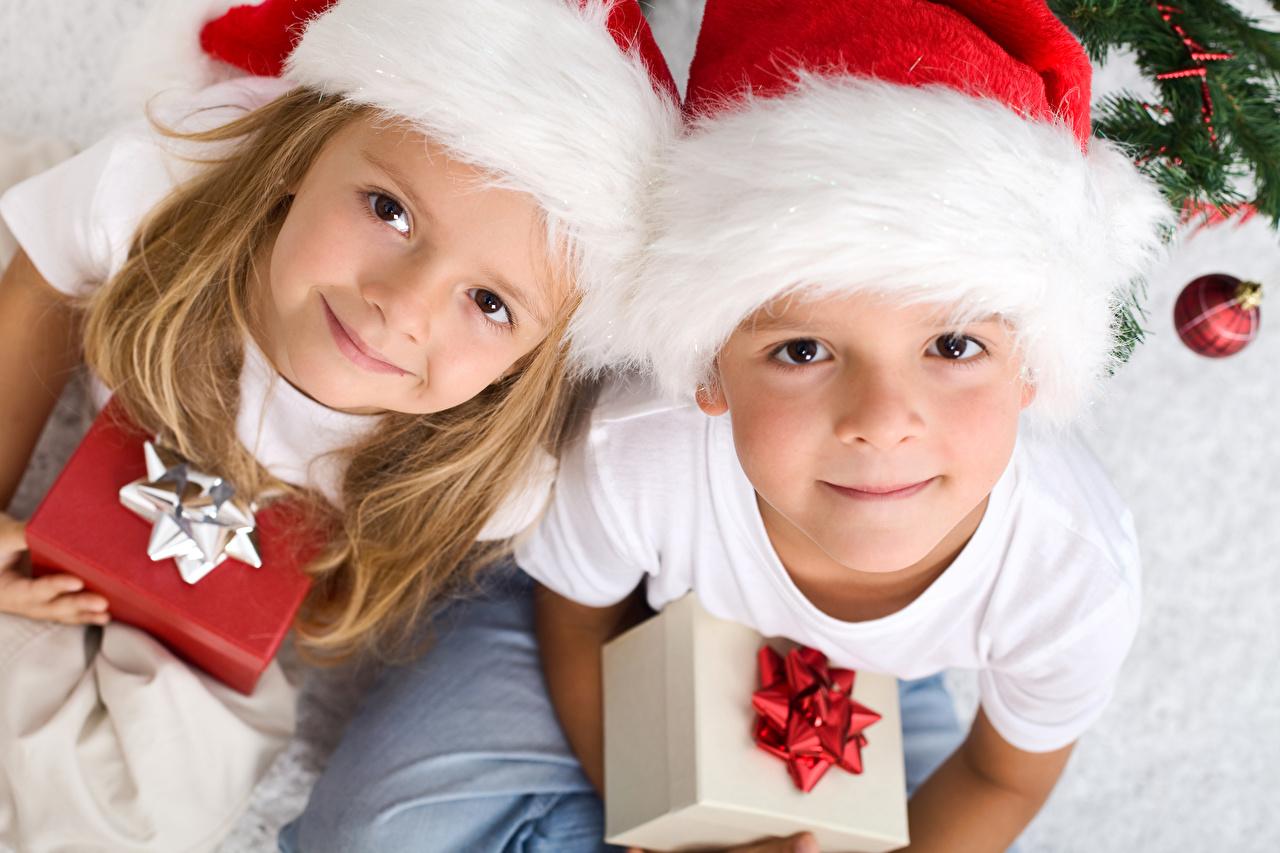 Картинка Девочки мальчик Новый год Дети две Шапки Подарки Взгляд девочка Мальчики мальчишки мальчишка Рождество ребёнок 2 два Двое шапка вдвоем в шапке подарок подарков смотрят смотрит