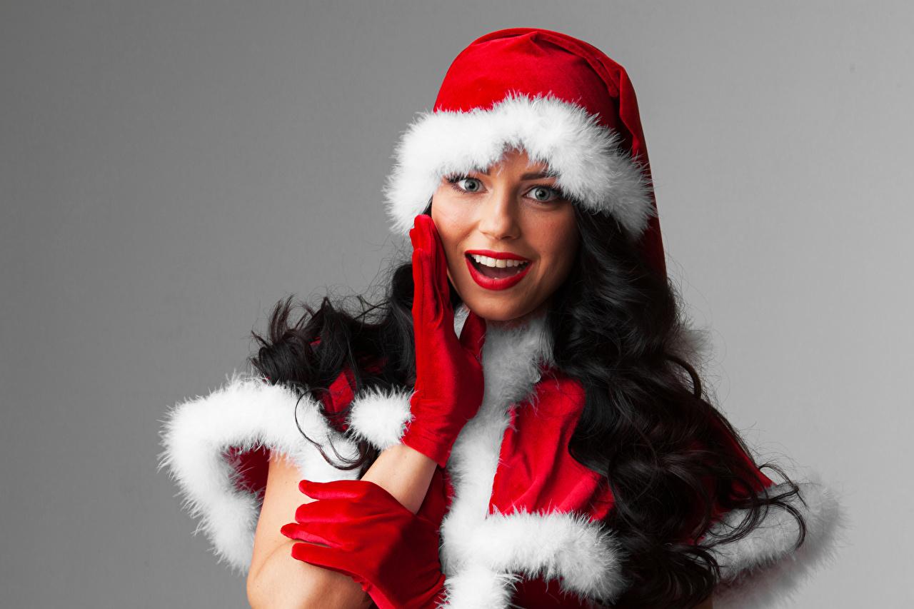 Фото Брюнетка Новый год Перчатки Шапки Девушки Взгляд Серый фон Рождество смотрит