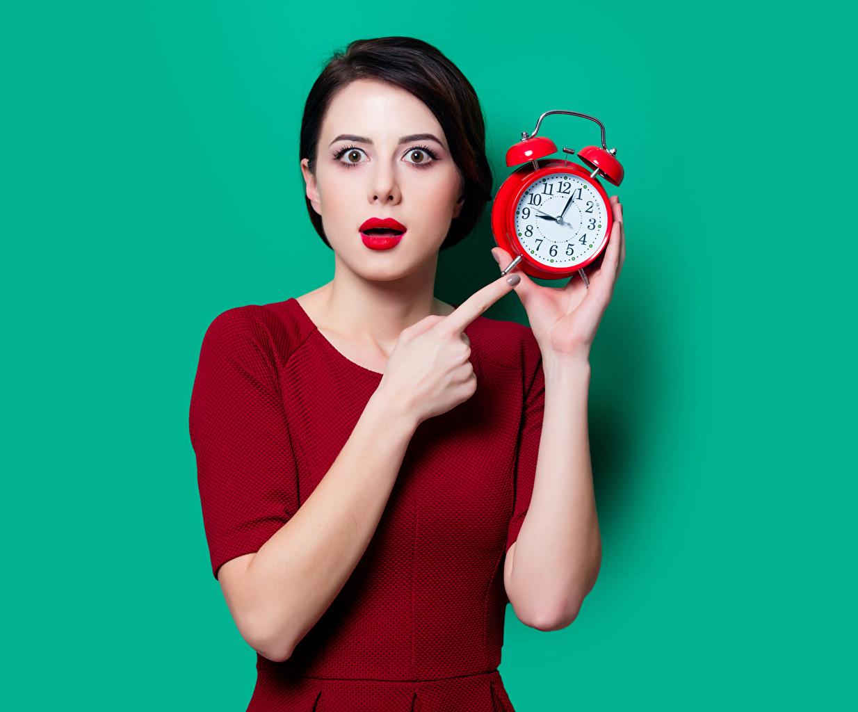Картинки брюнеток Часы молодая женщина Будильник Пальцы смотрит красными губами Цветной фон Брюнетка брюнетки девушка Девушки молодые женщины Взгляд смотрят Красные губы