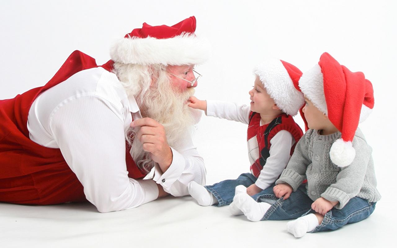 Обои мальчик Борода Ребёнок в шапке Дед Мороз Свитер Очки Сидит втроем Белый фон Мальчики мальчишки мальчишка Дети Шапки шапка Санта-Клаус очков Трое 3 очках сидящие