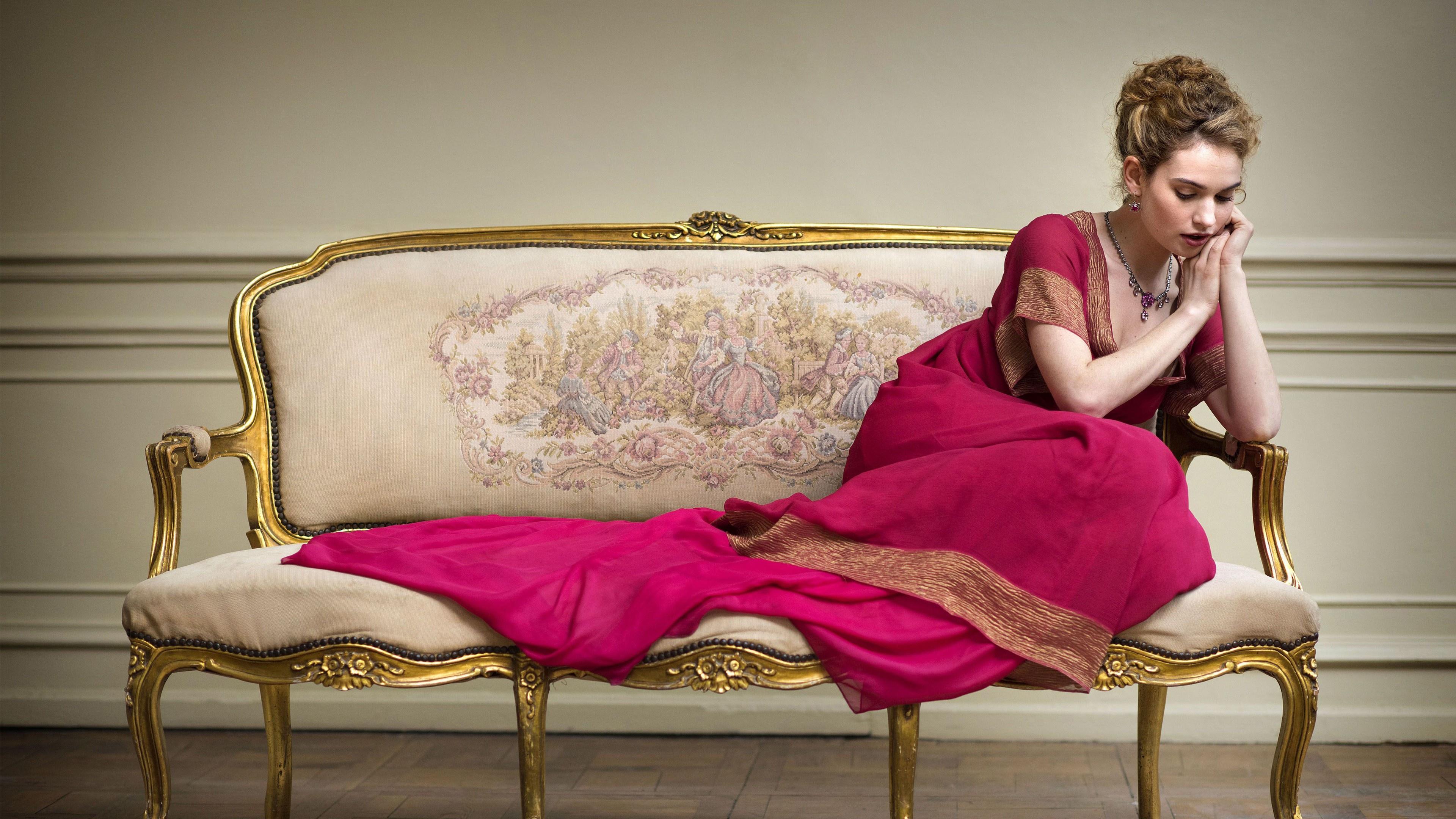 Фотографии Лили Джеймс молодая женщина диване сидящие Знаменитости платья 3840x2160 девушка Девушки молодые женщины сидя Диван Сидит Платье
