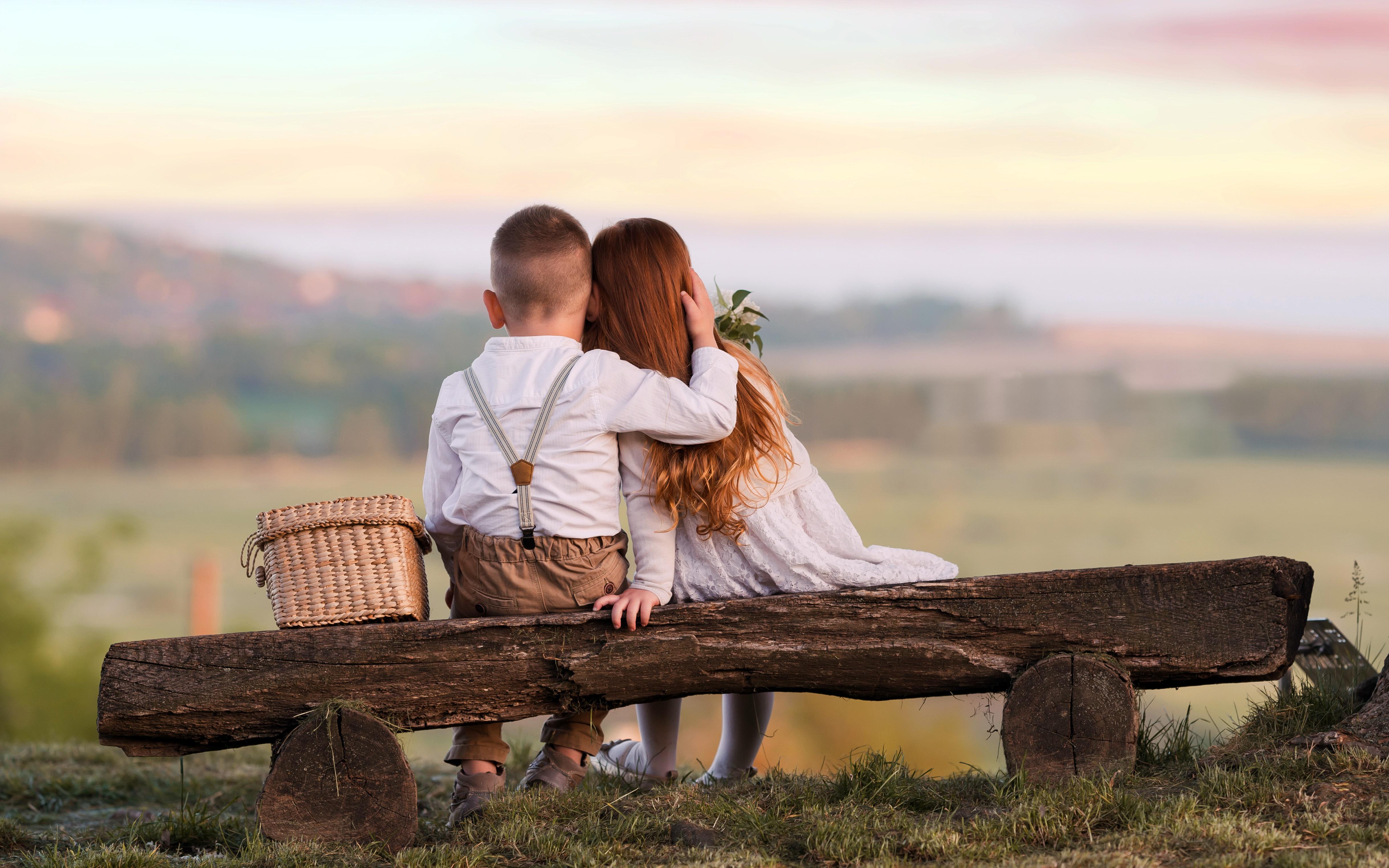 Фотография Девочки Мальчики Ребёнок Двое Любовь Объятие вид Скамья сидящие Дети 2 вдвоем Сидит Сзади Скамейка