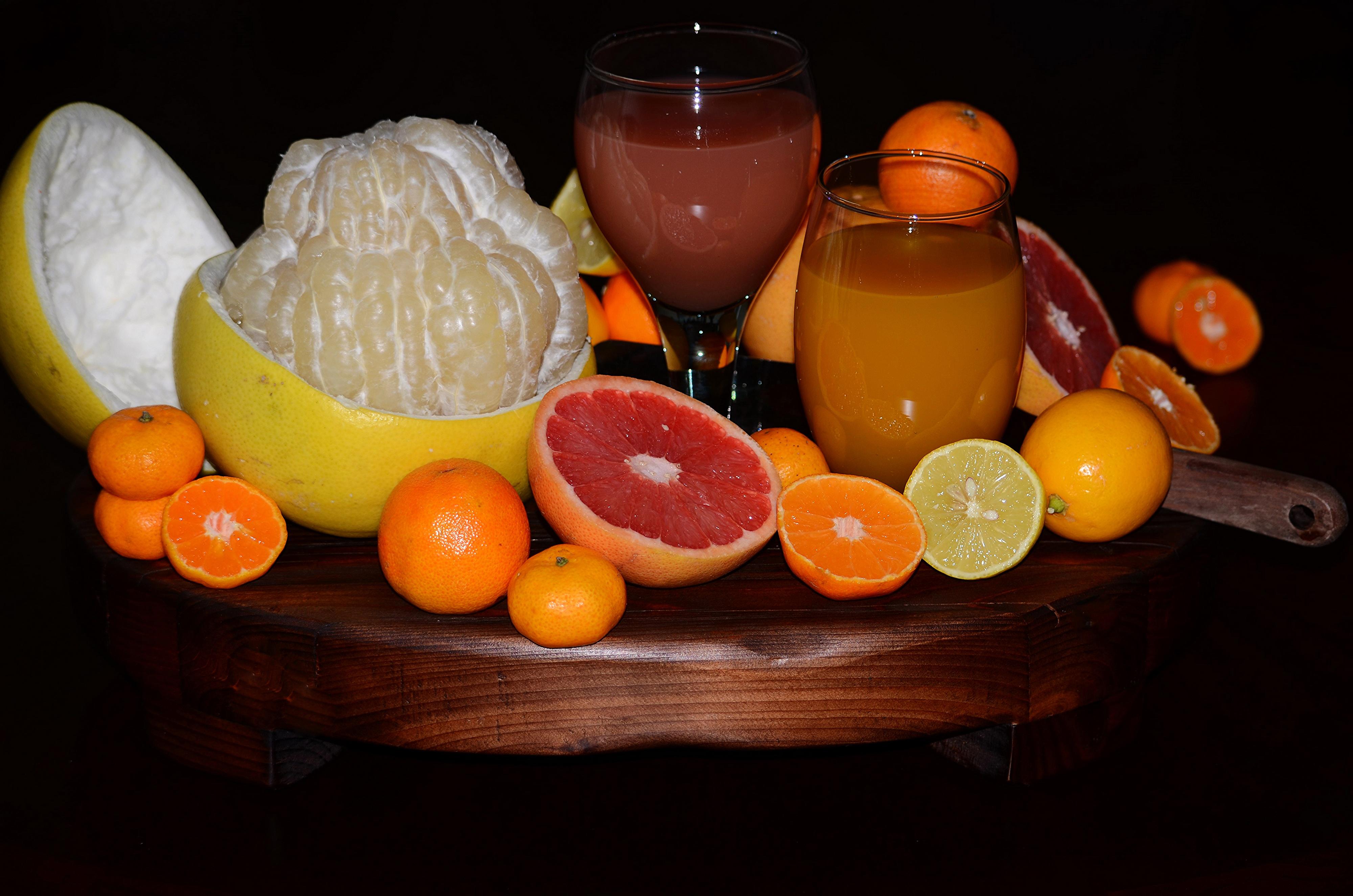 Фотография Сок Апельсин Грейпфрут Мандарины Стакан Лимоны Еда Черный фон Цитрусовые стакана стакане Пища Продукты питания на черном фоне