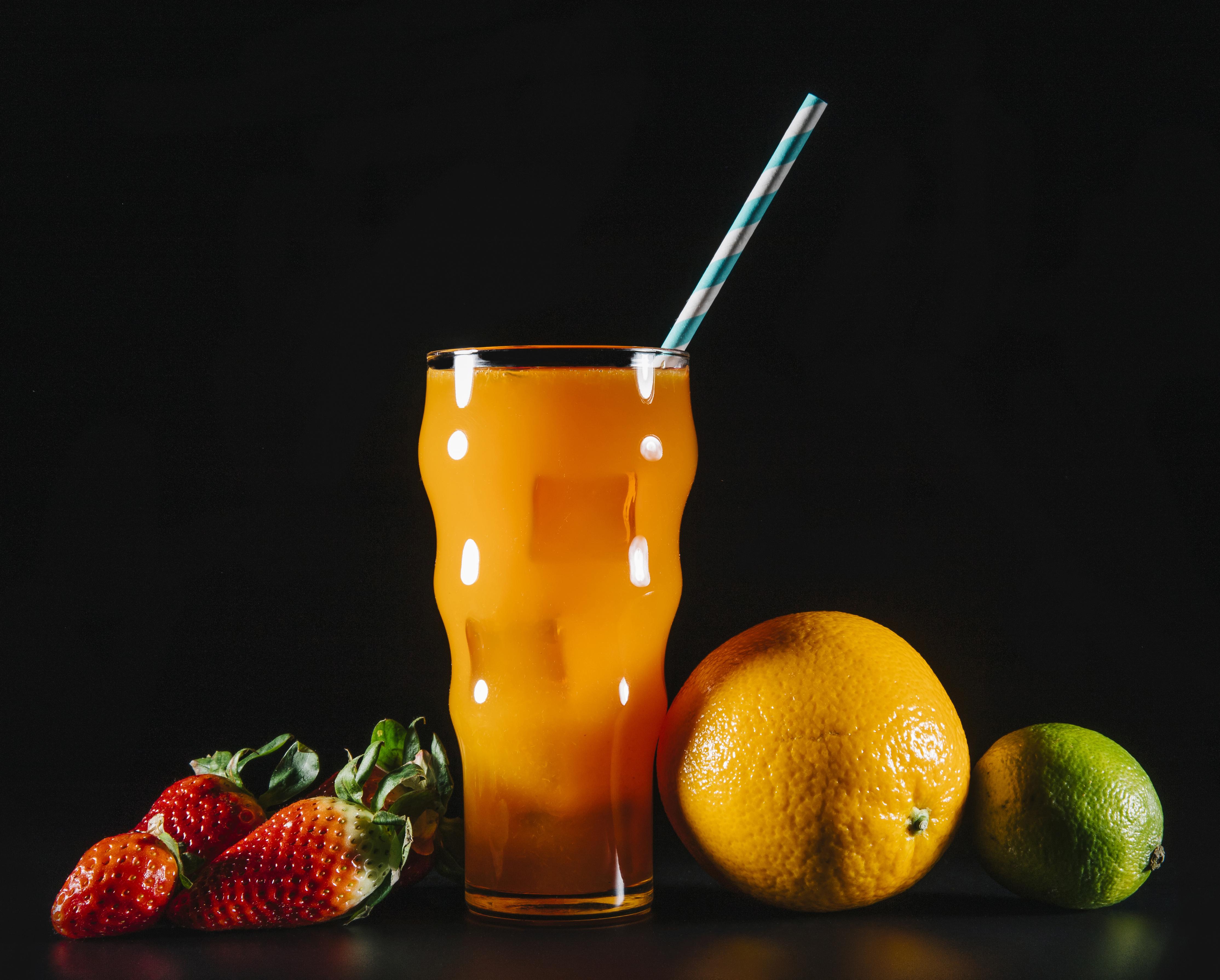 Фотографии Сок Лайм Апельсин стакана Клубника Еда на черном фоне Стакан стакане Пища Продукты питания Черный фон