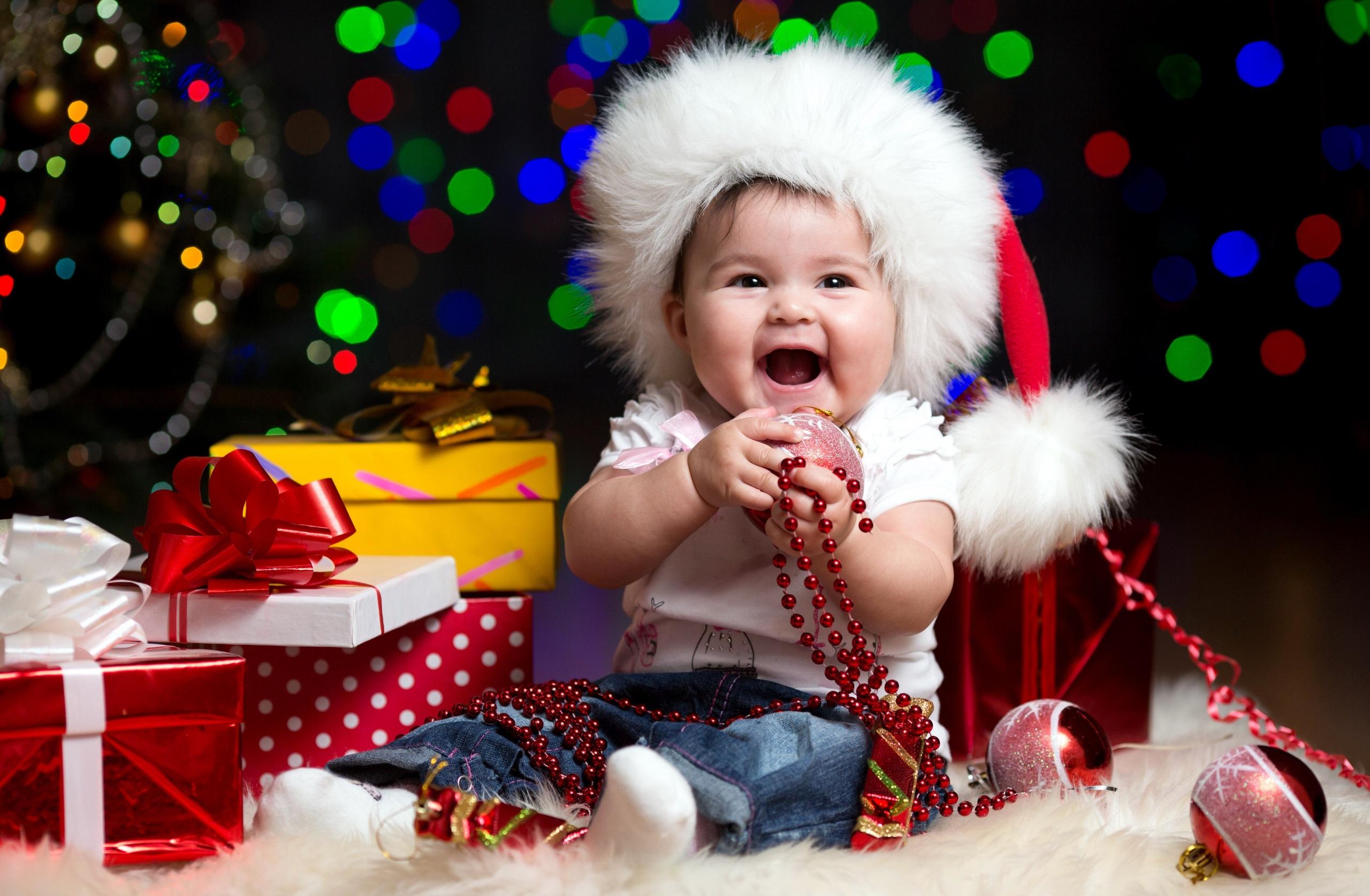 Фотография грудной ребёнок Рождество Радость Дети Шапки подарков бант Сидит Шарики 2560x1674 младенца младенец Младенцы Новый год счастье счастливые Ребёнок шапка в шапке Подарки подарок Шар сидя Бантик сидящие бантики