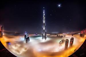 Картинки Небоскребы ОАЭ Здания Звезды Дубай Туман Ночь Burj Khalifa город