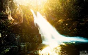 Картинка Водопады Камни Лучи света Aaron Woodall Природа
