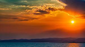 Картинка Море Рассветы и закаты Горы Небо Пейзаж Облака Солнце Природа