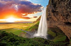 Фото Исландия Водопады Рассветы и закаты Пейзаж Скала Облака Seljalandsfoss Природа