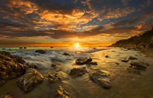 Картинка США Пейзаж Побережье Рассветы и закаты Камни Облака Солнце Горизонт Malibu Природа