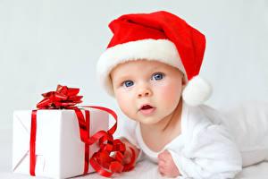 Картинка Новый год Младенцы Шапки Подарки Смотрит ребёнок