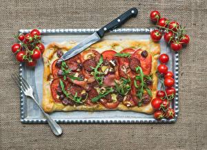 Фотографии Быстрое питание Пицца Помидоры Нож Колбаса Вилка столовая Продукты питания