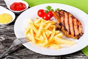 Фотографии Вторые блюда Мясные продукты Картофель фри Томаты Тарелка Продукты питания