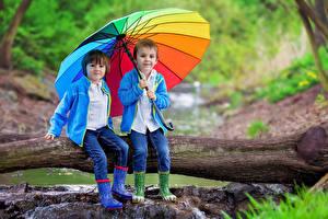 Фотография Мальчики Двое Зонт Джинсы Сапоги Ствол дерева Сидящие Ребёнок
