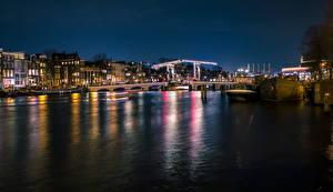 Картинка Амстердам Нидерланды Здания Реки Мосты Пирсы Ночные