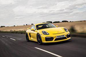 Фото Porsche Желтых Едущая Cayman GT4 Автомобили