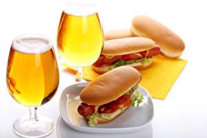 Фотографии Натюрморт Пиво Хот-дог Булочки Два Бокал Белом фоне Продукты питания