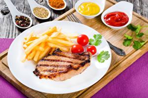 Фотографии Мясные продукты Картофель фри Помидоры Тарелка Кетчуп Разделочная доска Пища