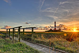 Фотография Германия Маяк Рассвет и закат Мост Небо Лучи света Облако Трава Westerhever Природа