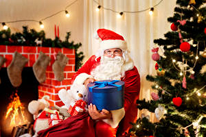 Картинки Праздники Новый год Санта-Клаус Шапки Коробка Подарки Очки Новогодняя ёлка Камин