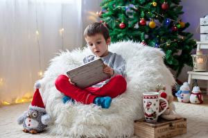Обои Новый год Мальчики Кресло Кружка Сидит Дети фото