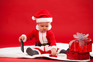 Картинки Рождество Младенец Униформа Дед Мороз Шапки Подарки Телефон Сидит Красном фоне ребёнок
