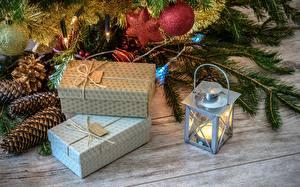 Картинки Рождество Праздники Свечи Подарки Коробка Лампа Ветвь Шишки Электрическая гирлянда