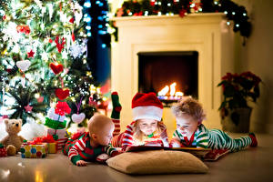 Картинка Рождество Праздники Девочка Мальчик Младенца Елка Шапка Камина Подарков Подушки Втроем ребёнок