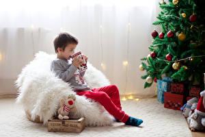Обои Новый год Праздники Мальчики Кресло Елка Подарки Кружка Дети фото