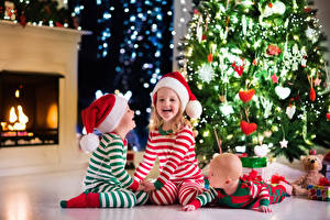Фотографии Рождество Мальчики Девочки Шапки Улыбка Младенцы Елка Трое 3 Камины Дети