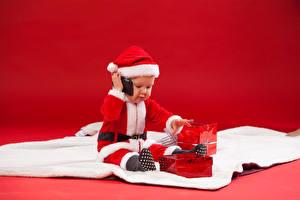 Фотография Новый год Грудной ребёнок Униформе Шапки Подарки Красный фон ребёнок