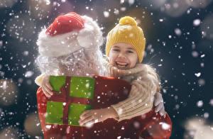 Картинка Новый год Подарки Санта-Клаус Девочки Шапки Снег Смех Счастливые Ребёнок