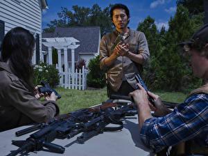 Обои Ходячие мертвецы Мужчины Пистолеты Стивен Ён Glenn Фильмы Знаменитости фото