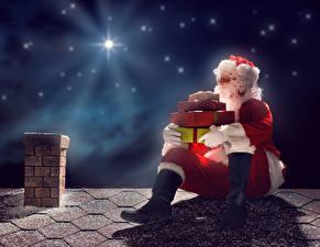 Картинки Рождество Небо Звезды Санта-Клаус Униформа Подарок В ночи Крыша Сидя