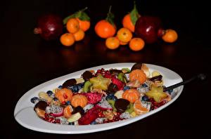 Фотография Мандарины Салаты Гранат Фрукты На черном фоне Тарелка Продукты питания