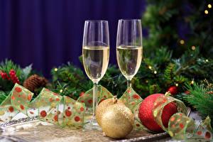 Картинки Рождество Праздники Игристое вино Бокалы Двое Ветки Шар Еда