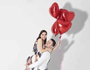 Обои День всех влюблённых Мужчины Любовь Белым фоном Шатенки Объятие Две Воздушный шарик Сердце Улыбка девушка